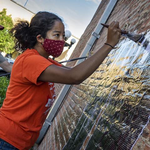 A girl in a masks paints a mural on a the brick exterior of a building