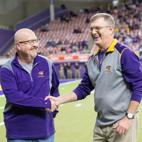 President Nook recognizes a UNI alumni educator at a UNI football game.
