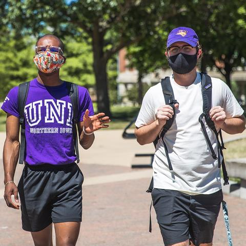 Two students in masks walk across the UNI campus on a sunny day