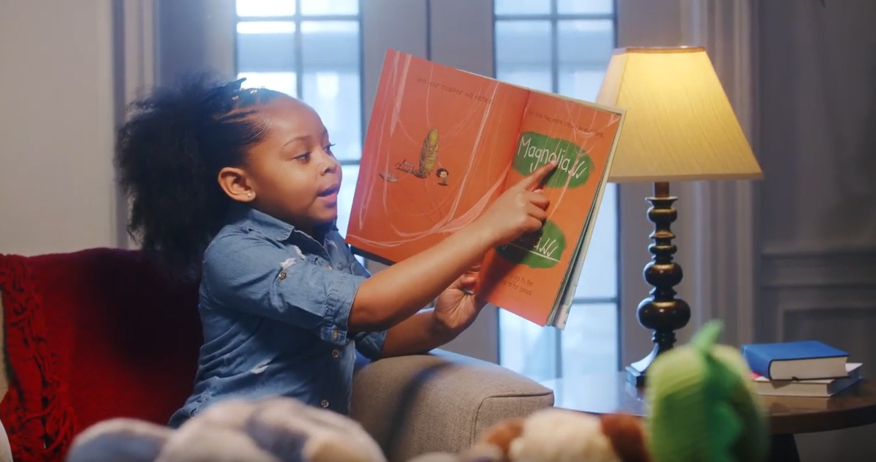 A young girl reads to her stuffed animals
